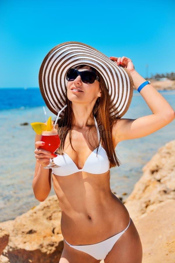 美丽的长发年轻女人在白色游泳衣、太阳镜和宽广边缘红海海岸海滩的与饮料玻璃,关闭 库存图片