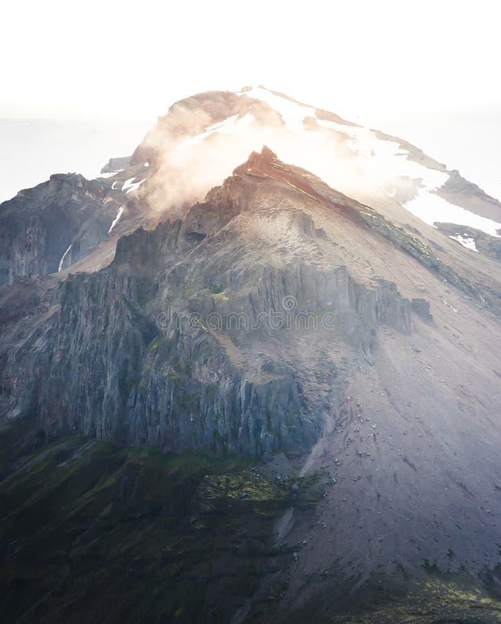 美丽的陡峭的小山和多雪的山与惊人的天空 免版税图库摄影
