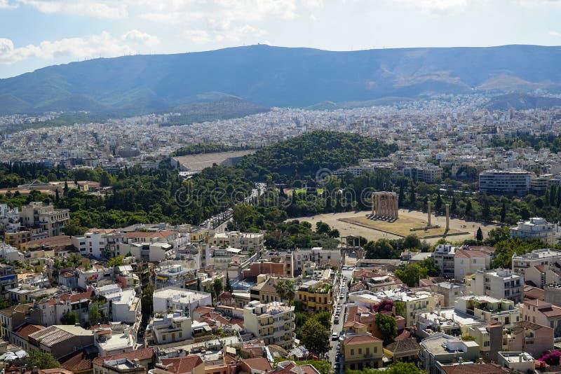美丽的雅典市全景从看见古老废墟,修造的建筑学,都市街道,树,山的上城的 免版税库存照片