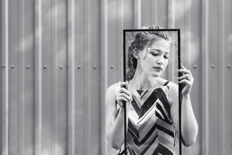 美丽的青少年的女孩在她的手上的拿着残破的玻璃 克服在青春期的挑战的概念 库存图片