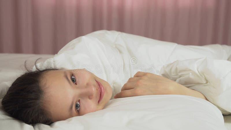 美丽的青少年的女孩在床和微笑上醒 免版税库存图片