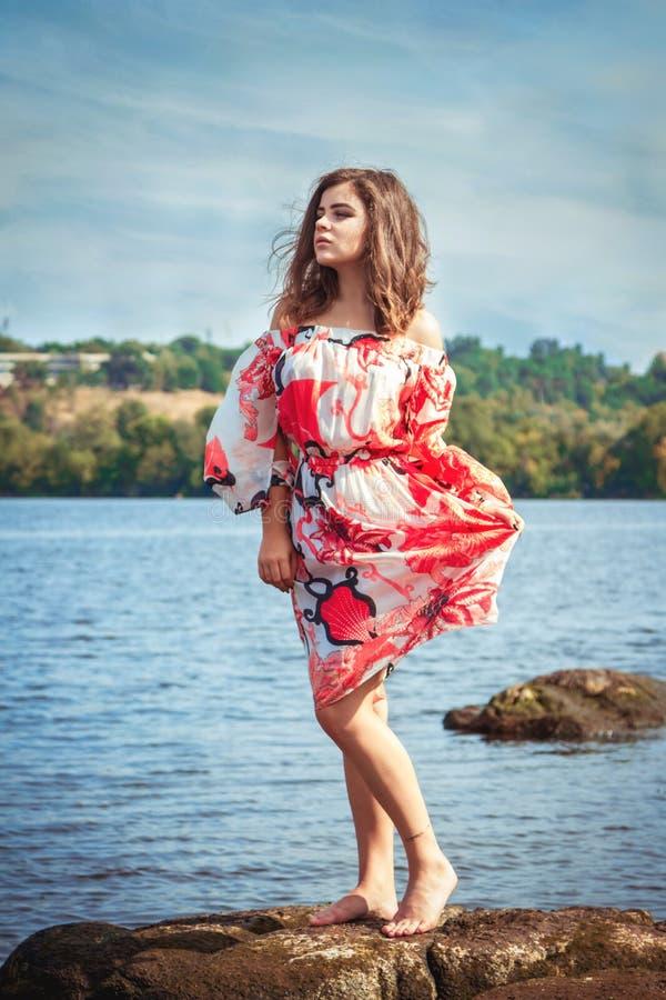 美丽的青少年的女孩,赤足站立在石头 库存图片