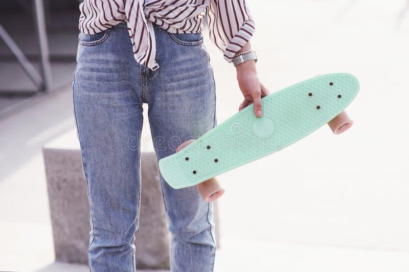 美丽的青少年的女性溜冰者坐舷梯在冰鞋公园 夏天都市活动的概念 免版税库存图片