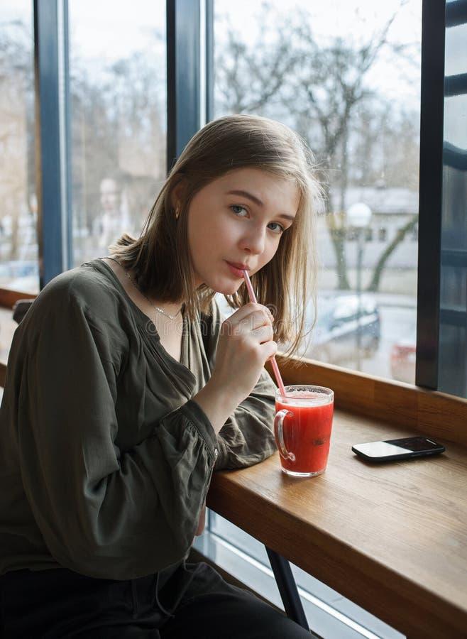 美丽的青少年的学生女孩画象的关闭有一个玻璃杯子的通过秸杆果子茶喝在坐在大附近的街道咖啡馆 库存图片