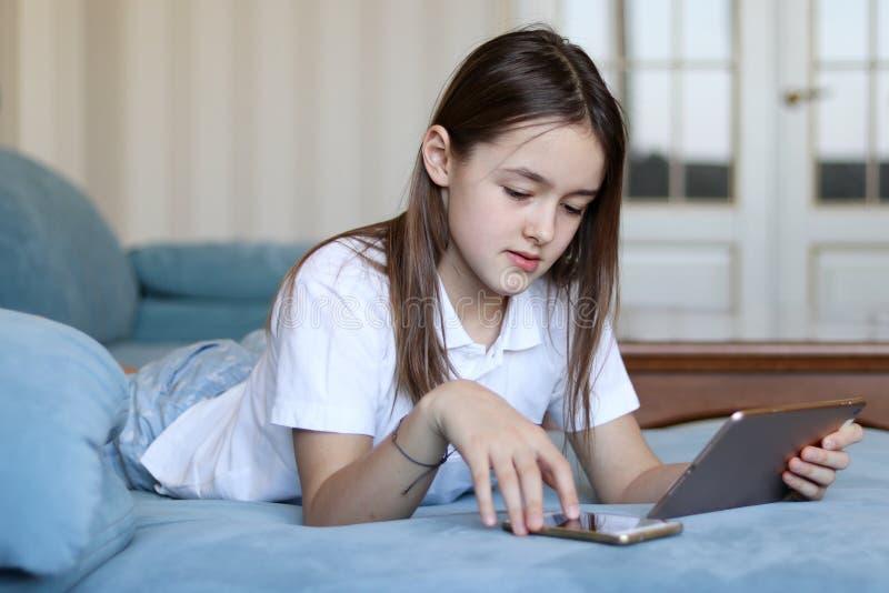 美丽的青春期前的她的智能手机和压料板女孩触摸屏  免版税库存图片