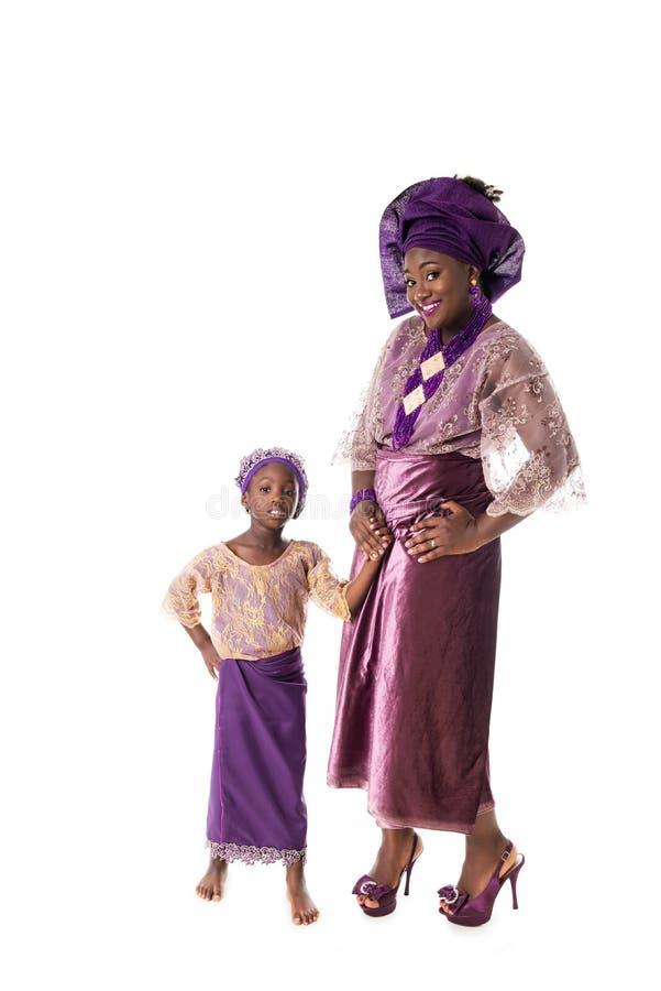 美丽的非洲妇女和可爱的小女孩传统衣物的,被隔绝 免版税库存图片