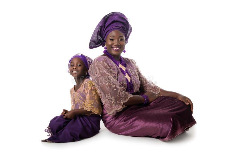 美丽的非洲妇女和可爱的小女孩坐地板 免版税图库摄影