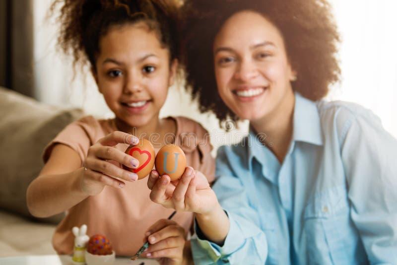 美丽的非裔美国人的上色复活节彩蛋的妇女和她的女儿 图库摄影