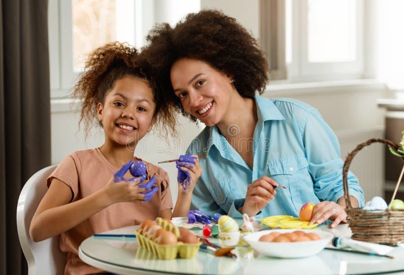 美丽的非裔美国人的上色复活节彩蛋的妇女和她的女儿 库存照片