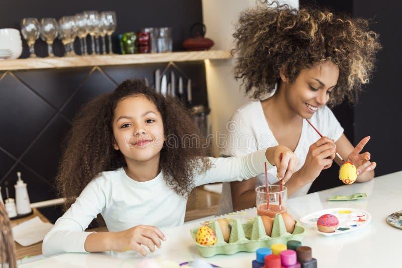 美丽的非裔美国人的上色复活节彩蛋的妇女和她的女儿在厨房里 免版税图库摄影