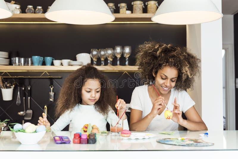 美丽的非裔美国人的上色复活节彩蛋的妇女和她的女儿在厨房里 库存图片
