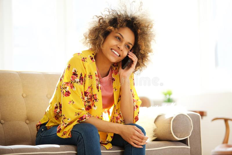 美丽的非裔美国人的女孩坐长沙发谈话在手机 库存图片