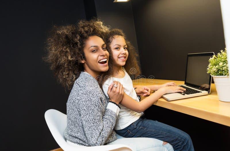 美丽的非裔美国人的妇女和她的使用膝上型计算机的女儿 免版税库存图片