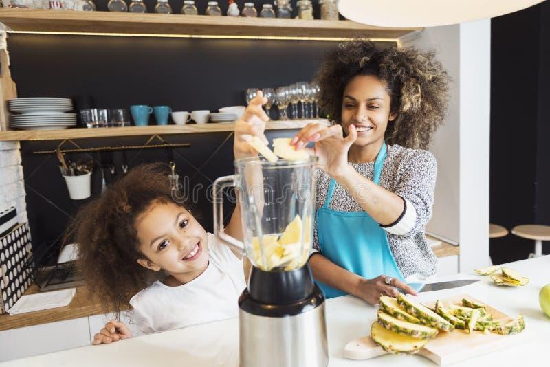 美丽的非裔美国人的妇女和她的女儿切口在厨房里结果实 免版税图库摄影