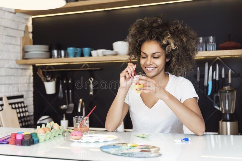 美丽的非裔美国人的妇女着色鸡蛋 库存图片