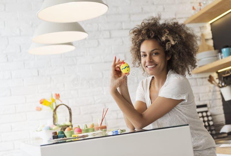美丽的非裔美国人的妇女着色鸡蛋 图库摄影