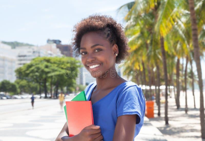 美丽的非裔美国人的学生在城市 免版税图库摄影