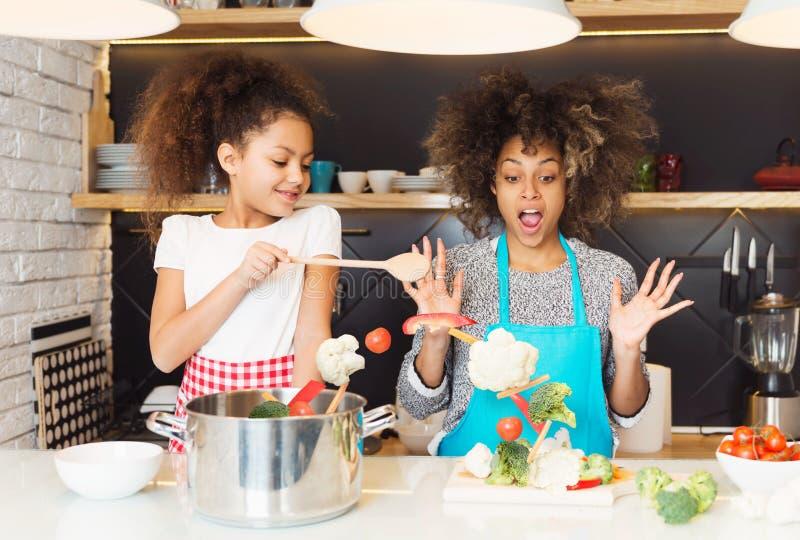 美丽的非裔美国人的烹调在厨房里的妇女和她的女儿 免版税库存图片