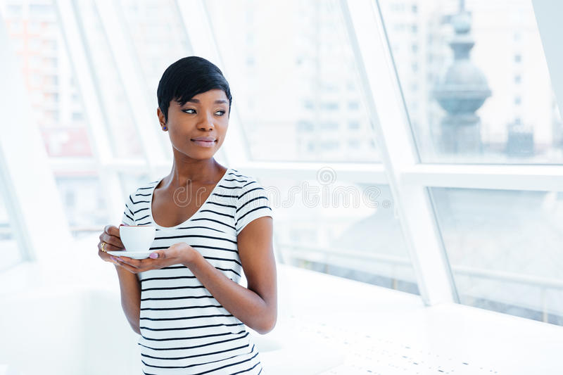 美丽的非裔美国人的年轻女实业家站立的和饮用的咖啡 库存照片