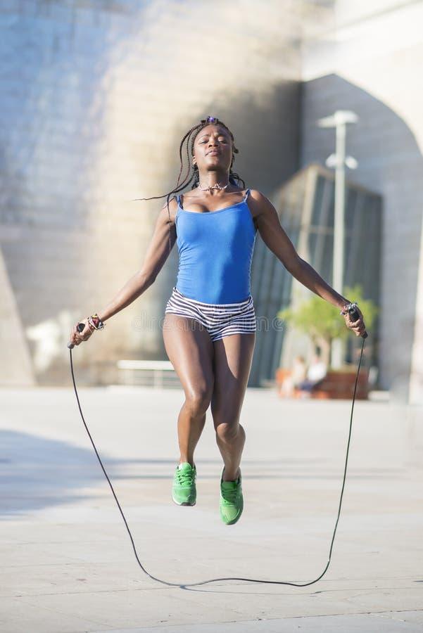 美丽的非洲体育妇女跳绳,健康生活方式co 免版税库存图片