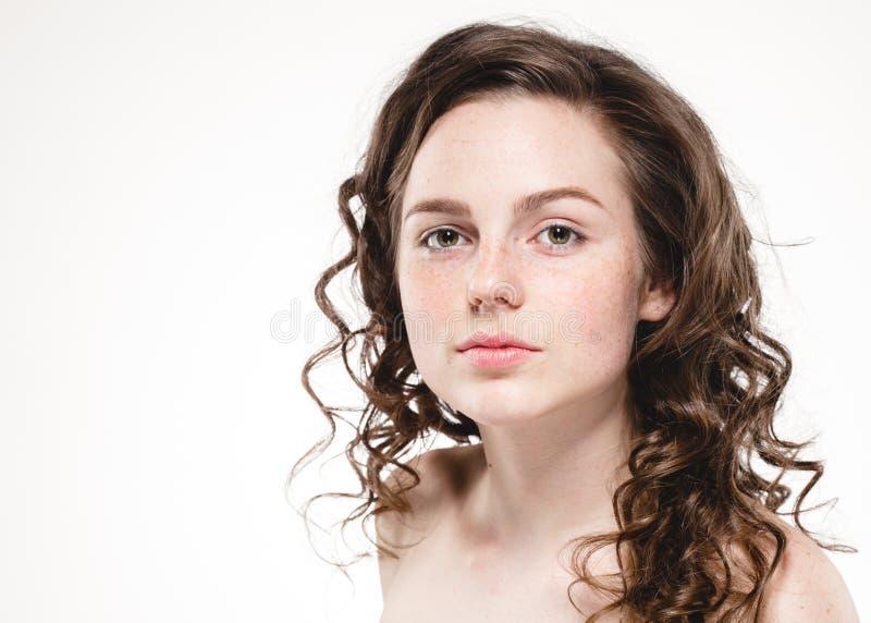 美丽的面孔妇女雀斑和卷曲飞行头发 免版税库存照片