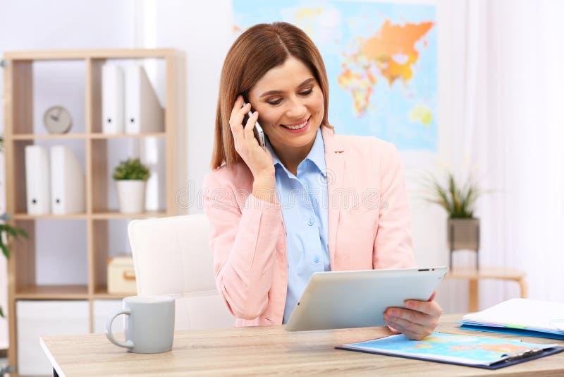 美丽的顾问谈话在电话 旅行社 库存照片