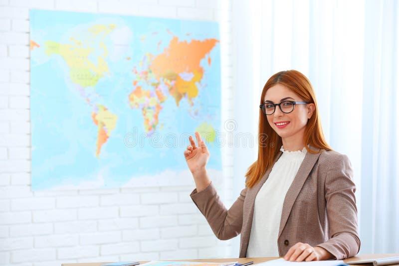 美丽的顾问陈列地图在旅行公司中 免版税库存照片