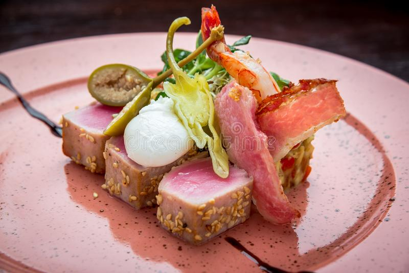 美丽的食物:在芝麻、石灰和新鲜的沙拉特写镜头的牛排金枪鱼在板材 免版税库存图片