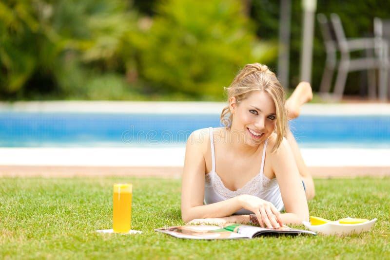 美丽的饮用的汁液橙色妇女年轻人 库存图片