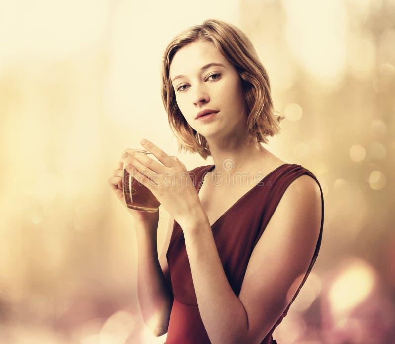 美丽的饮用的茶妇女年轻人 库存照片