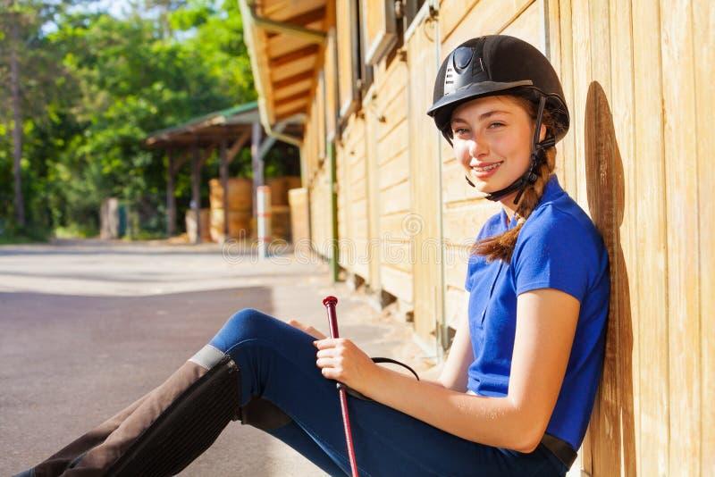 美丽的骑师女孩画象马棚的 库存图片