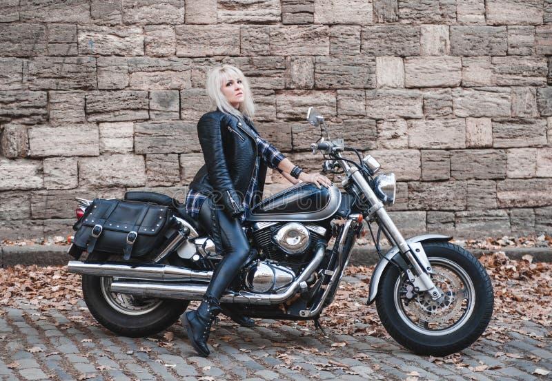 美丽的骑自行车的人妇女室外与摩托车 免版税库存图片