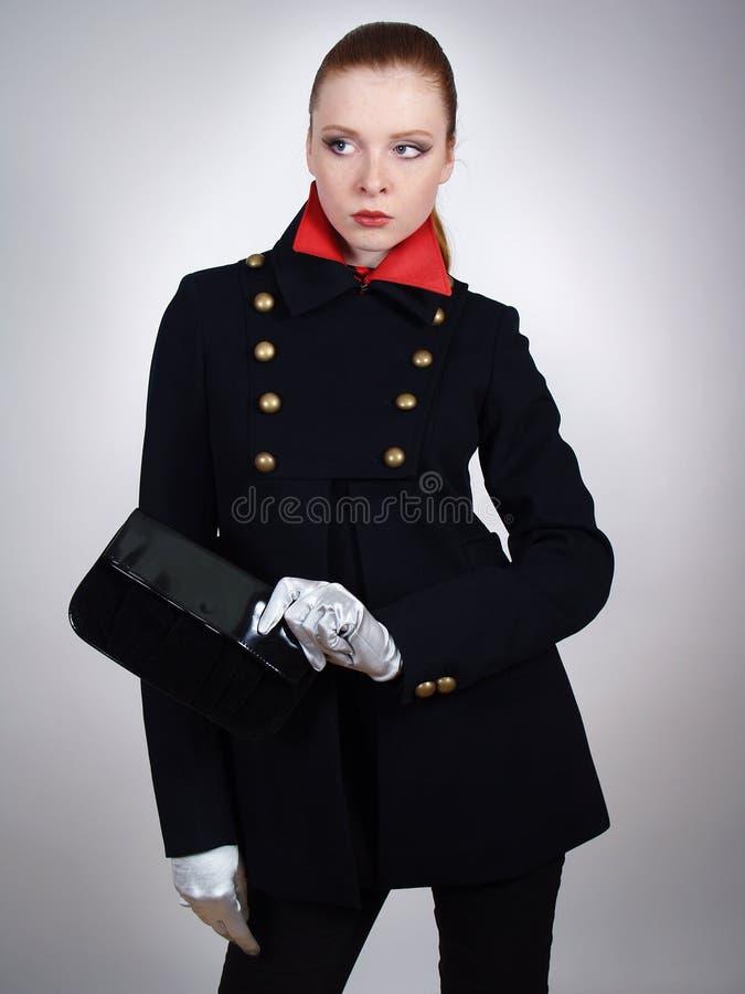 美丽的黑色外套短小妇女年轻人 免版税库存照片