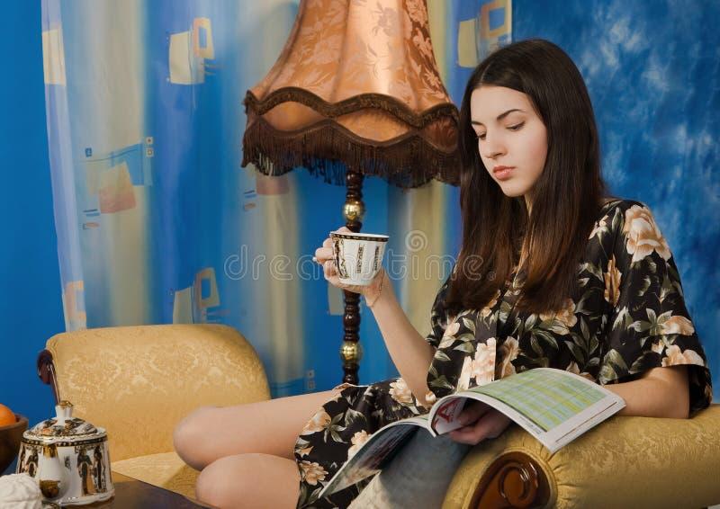 美丽的黑色饮用的女孩茶 免版税库存图片