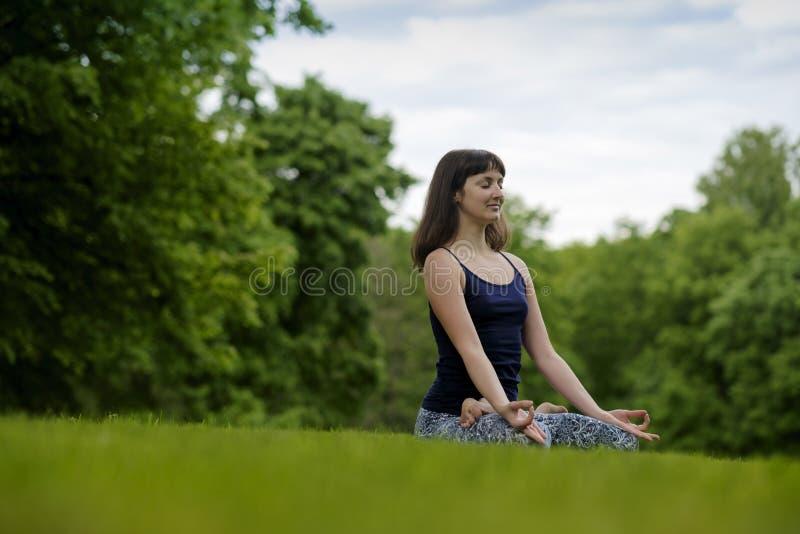 美丽的,坐与在莲花姿势的盘的腿在公园在夏日的年轻人适合的妇女思考,呼吸 免版税库存图片