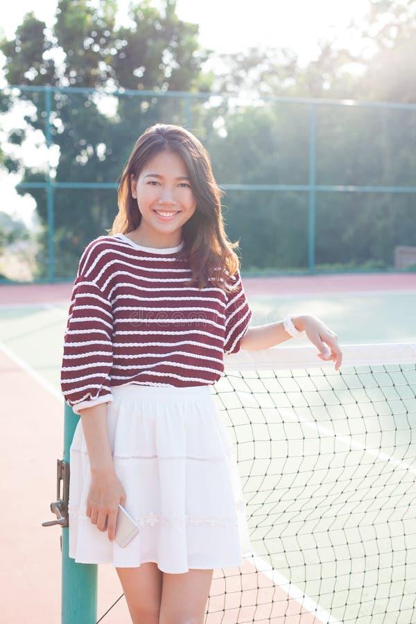美丽的年轻亚裔在网球路线的妇女佩带的白色衣裳裙子画象与愉快的面孔 免版税图库摄影