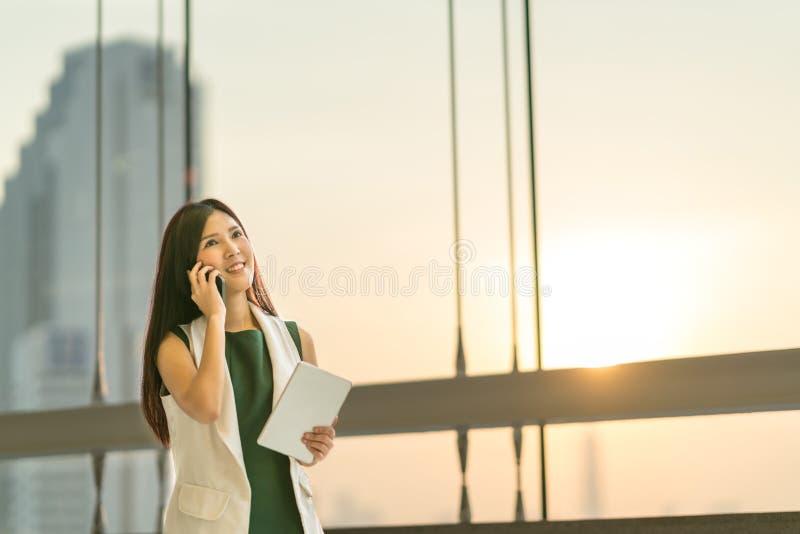 美丽的年轻亚洲女实业家用途智能手机和数字式片剂向上看复制空间 免版税库存照片