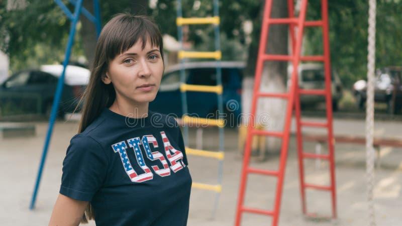 美丽的年轻俏丽的妇女画象有全国美国旗子的在T恤杉 免版税库存图片