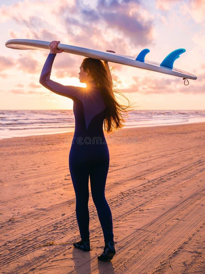 美丽的头发长的妇女年轻人 冲浪有冲浪板的女孩在海滩在日落或日出 冲浪者和海洋 图库摄影