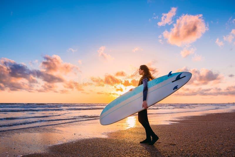 美丽的头发长的妇女年轻人 冲浪有冲浪板的女孩在海滩在日落或日出 冲浪者和海洋 免版税库存照片