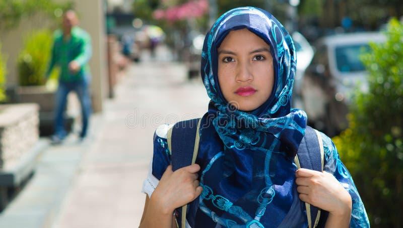 美丽的年轻回教妇女佩带的蓝色上色了hijab和背包,摆在与周道的严肃的表情 库存照片
