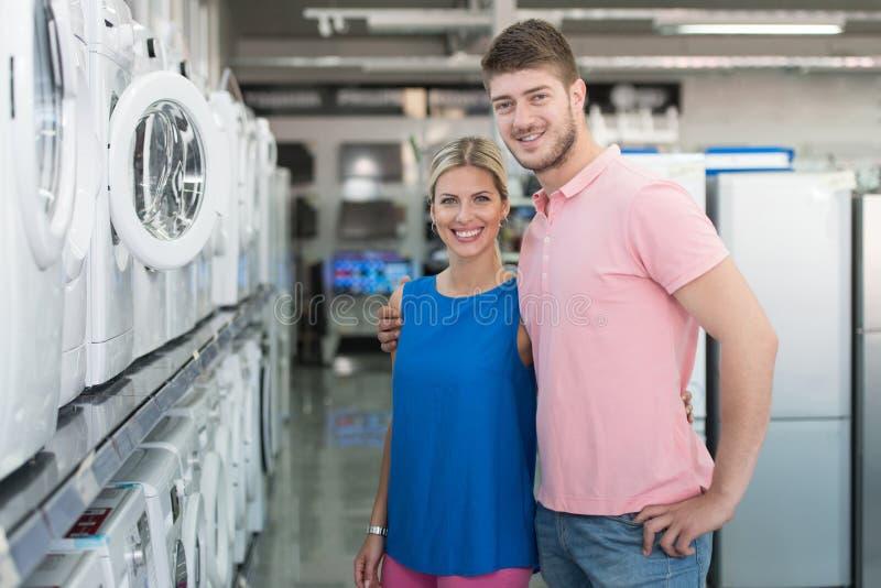 美丽的年轻夫妇购物洗衣机在超级市场 免版税图库摄影