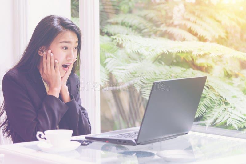 美丽的年轻女商人与膝上型计算机一起使用,看有欣喜姿态的屏幕,震动,惊奇情感 免版税库存照片