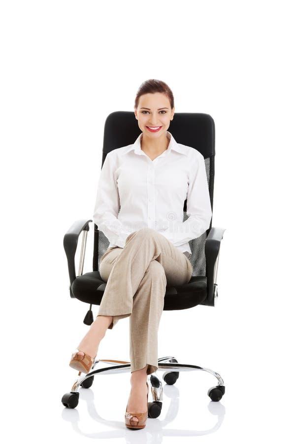美丽的年轻女商人坐椅子。 库存照片