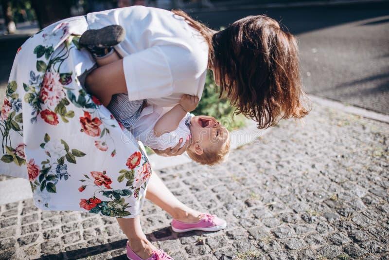 美丽的年轻妈妈和快乐的可爱的白肤金发的男孩使用,获得乐趣 妇女爱她的儿子 免版税库存图片