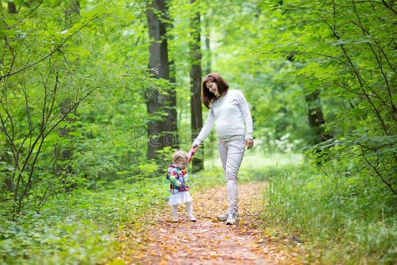 美丽的年轻孕妇和她的小女儿 免版税库存照片