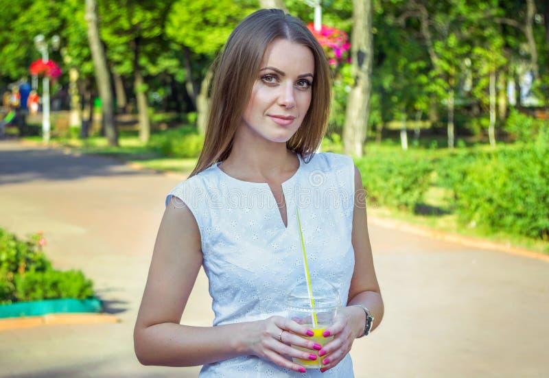 美丽的年轻微笑的妇女,拿着柠檬水鸡尾酒 免版税库存图片