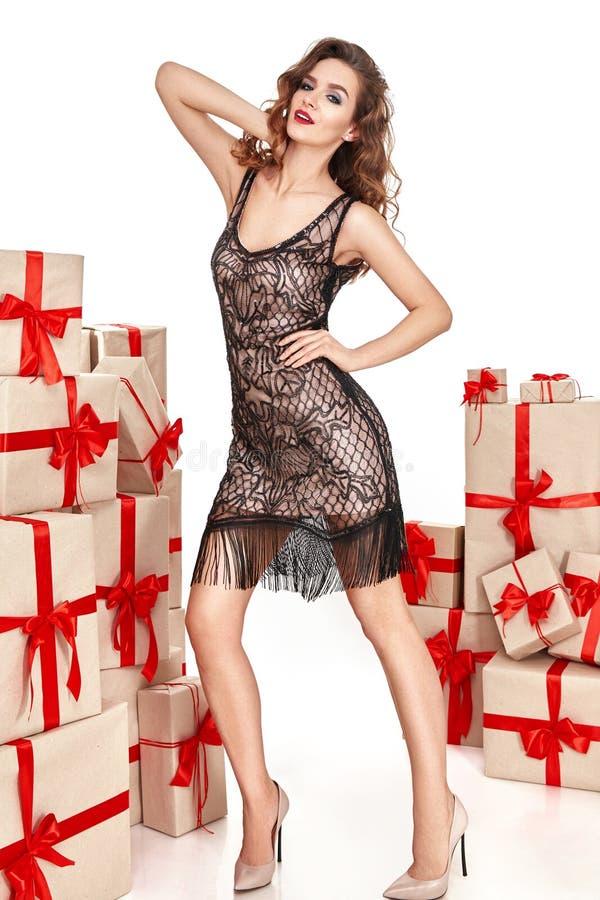 美丽的年轻性感的妇女稀薄的微小的形象晚上构成时兴的时髦的外套,衣物汇集,浅黑肤色的男人,礼物盒关于 库存照片