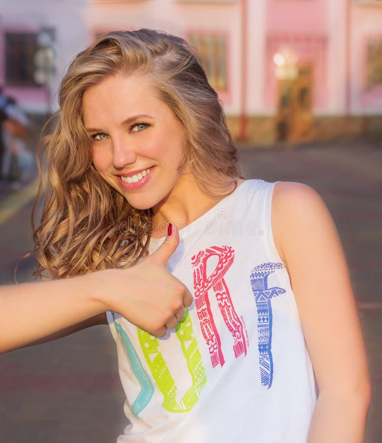 美丽的年轻愉快的微笑的女孩在城市的街道上的温暖的夏日显示字符类别象 库存照片