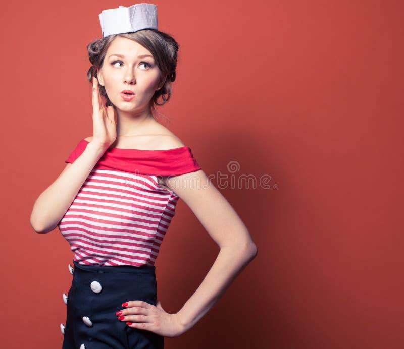 美丽的画报女孩打扮了摆在红色背景的水手 库存照片